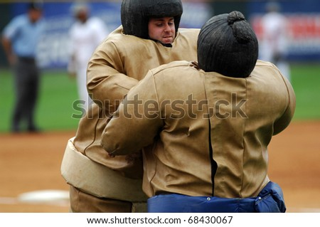 CAMDEN, NJ - AUGUST 15: Two fans dressed in Sumo Wrestler costumes compete during a contest between innings of an Atlantic League baseball game August 15, 2010 in Camden, NJ.