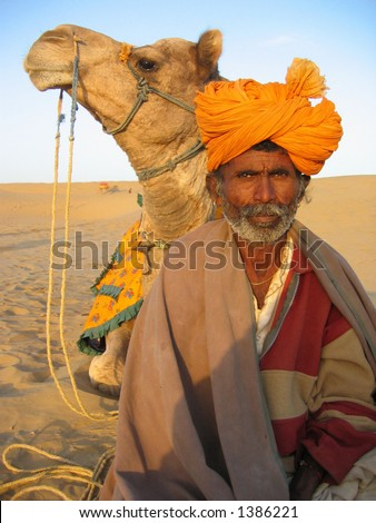 Camel and owner rest during desert crossing in Sam, India.