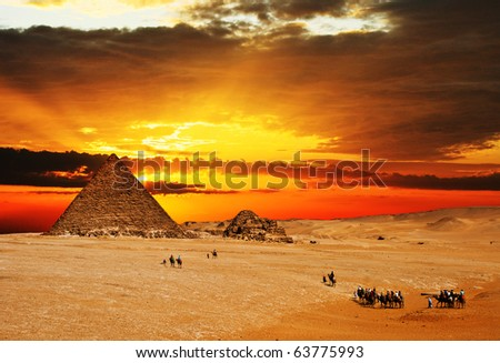 Camel caravan going through desert in front of pyramid at sunset ...