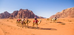 Camels caravan in majestic Wadi Rum, aka Valley of the Moon, a protected nature reserve with dramatic sandstone mountains and granite rock. The largest wadi in Jordan