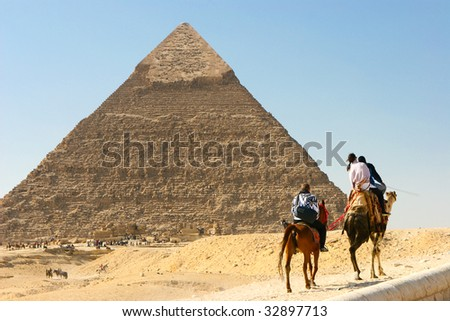 camels pass by the pyramid #32897713