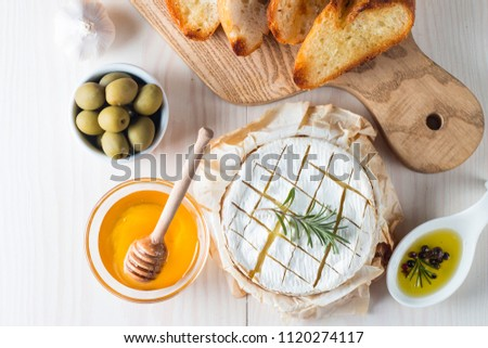 Camembert and brie cheese on wooden background with tomatoes, letuce and garlic. Italian food. Dairy products.