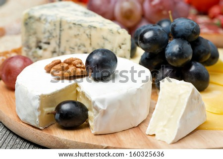 Camembert, blue cheese, grapes and walnuts, close-up
