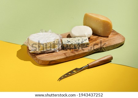 Camembert, blue cheese, mozzarella and pecorino: several cheese sorts on a wooden board on a colorful green and yellow background and a cheese knife                                                    Stock photo ©
