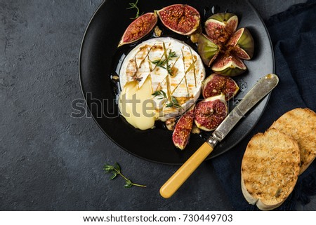 camembert cheese baked with  figs, nuts and honey, top view, black background