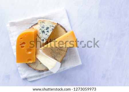 Camembert, hard yellow cheese and blue cheese on wooden board. Pieces of various cheeses on white napkin. Dorblu and soft cheese in style of minimalism. Dairy products