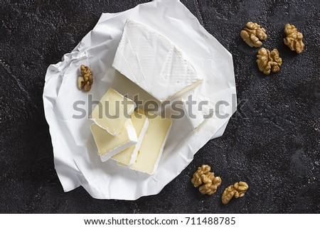 Camembert or brie cheese in white paper and walnut on black  background. Top view.