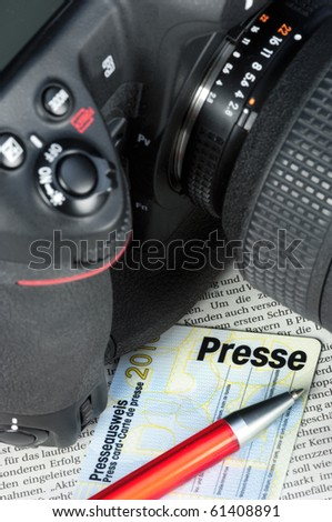 Camera and press card on a newspaper