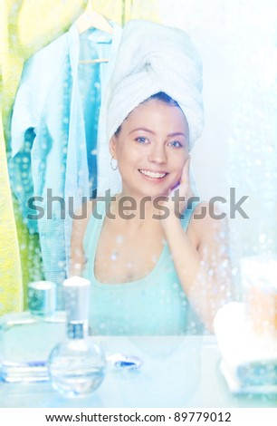 Camera behind the mirror - woman having a shower and smiling