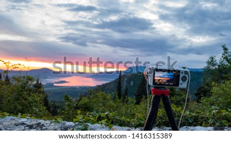 Camera capturing sunset shot. Photography using on tripod against sun rays with mountain in beautiful sundown scene. #1416315389