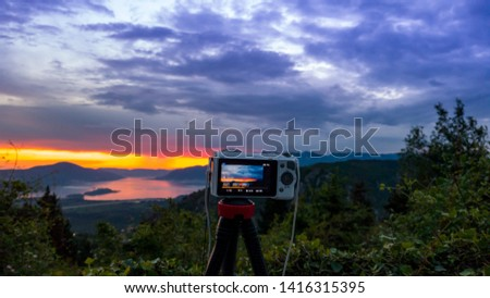 Camera capturing sunset shot. Photography using on tripod against sun rays with mountain in beautiful sundown scene. #1416315395