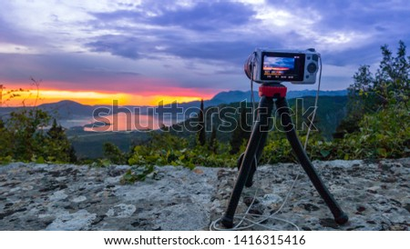 Camera capturing sunset shot. Photography using on tripod against sun rays with mountain in beautiful sundown scene. #1416315416