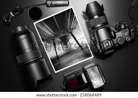 Camera equipment around a printed photo of a pier perspective