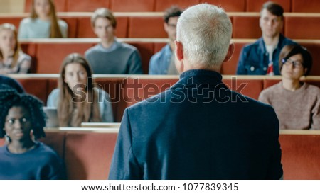 Camera Facing Class: College Professor Gives a Lecture to a Classroom Full of Multi Ethnic Students. Talented Speaker Captures Audience Attention.