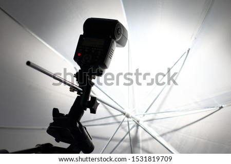 Camera flash flashes in a white umbrella in the photography studio. #1531819709