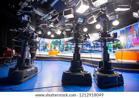 Camera in studio are broadcasting journalists reading news.Blur background have table for reporter.
