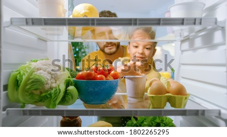 Camera Inside Kitchen Fridge: Dad Lifts Cute Little Daughter to Choose Whatever She wants to Take From the Fridge, She Chooses Healthy Yogurt. Point of View POV Shot from Refrigerator full of Food
