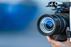 Camera lens attached to a camera and hand focusing close up detailed with smooth blue background and sunset reflections. Concept for videography cinematography vlogging video television movies making