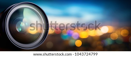Camera lens with lense reflections on blur night city. Media and technology concept background. #1043724799