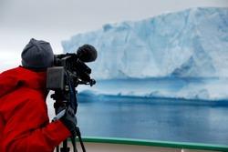 camera man filming an iceberg in antarctica