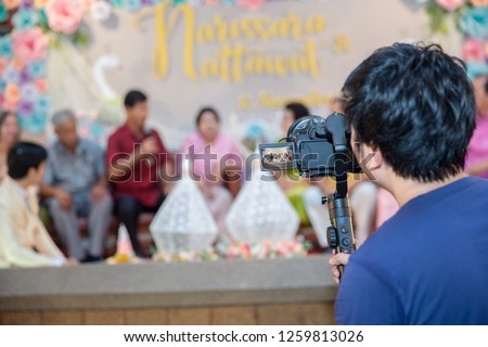 Camera man use steadicam with DSLR camera for video production are shooting movie in wedding ceremony. stabilize tool. stabilizer control machine. movie technology. image for background