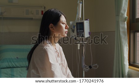 camera movement taiwanese female beside hospital window is gazing into distance and shedding tears. asian lady with rare disease sitting alone in ward is sad and losing courage. Stock photo ©