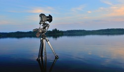 Camera on a tripod standing in water.Filming Nature.Sunset on the lake.