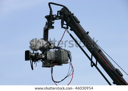 Camera on crane in action; blue sky as background