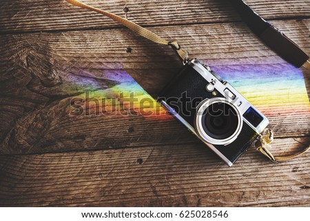 Camera on Wooden Table with Reflection of Prism Lights