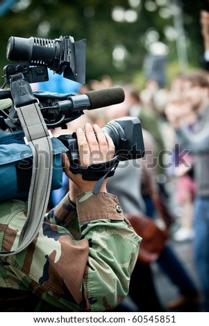Camera operator on reportage recording crowd