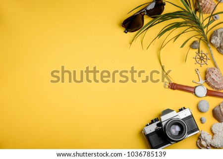 Camera, sunglasses and watches on yellow. Collecting seashells and capturing happy moments. Travel to the coast. #1036785139