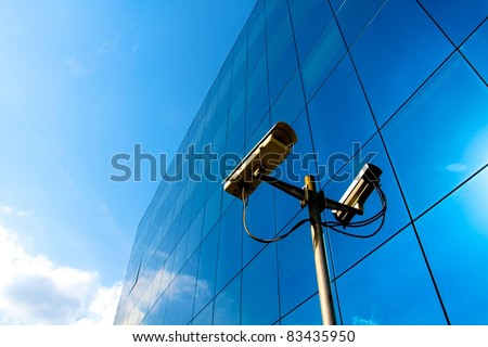 Camera system guarding blue skyscraper office building with sky above