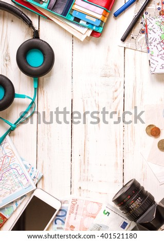 Camera, touristic maps, headphones, wallet with credit cards, phone, colorful pens, euro banknotes and coins on the white desk. Travel background. Journey planning. Tourist essentials. Space for text #401521180