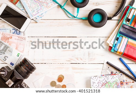 Camera, touristic maps, headphones, wallet with credit cards, phone, colorful pens, euro banknotes and coins on the white desk. Travel background. Journey planning. Tourist essentials. Space for text #401521318