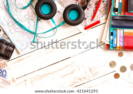 Camera, touristic maps, headphones, wallet with credit cards, phone, colorful pens, euro banknotes and coins on the white desk. Travel background. Journey planning. Tourist essentials. Space for text #421641295