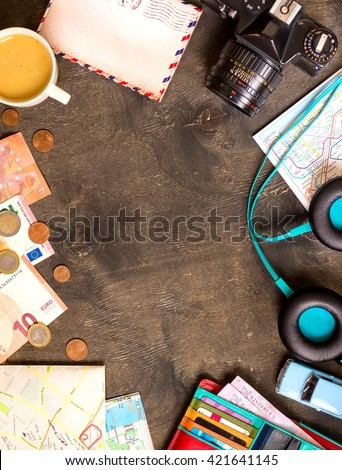 Camera, touristic maps, passport, toy car, coffee, headphones, wallet with credit cards, euro banknotes and coins on a black desk. Travel background. Tourist essentials. Plan a journey. Space for text #421641145