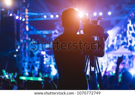 Cameraman shooting video action film production camera videographer in concert music festival #1070772749