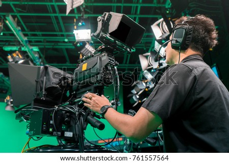 Cameraman taking a broadcast camera in broadcast television virtual green screen studio room. #761557564