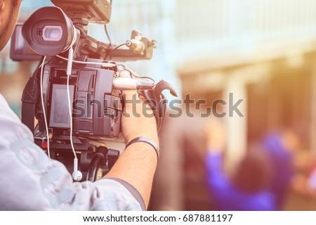 Cameraman using black professional digital video camera. Outdoor setup and working #687881197