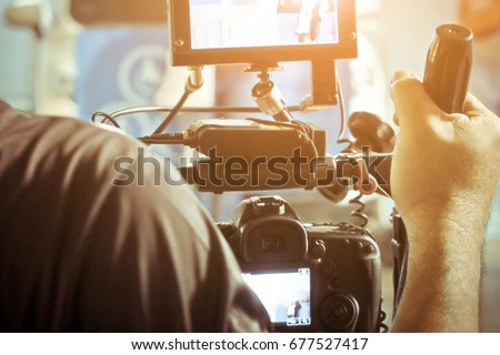 Cameraman with his video camera shooting, Hands Adjusting Camera,film production crew,behind the scenes background. #677527417