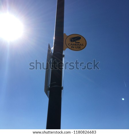 Cameras in Use sign on a tall pole in parking lot with blaring sun
