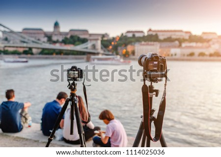 Cameras on tripods photograph a bridge and a river in the city of Budapest. Concept training and Workshop or masterclass on landscape and city photography.