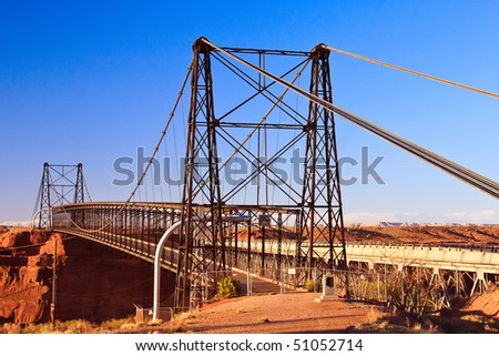 Cameron Suspension Bridge spans the Little Colorado River upstream from the Grand Canyon. In 1958, the Hwy Bridge was built alongside, and the old suspension bridge was converted to a pipeline bridge. - stock photo