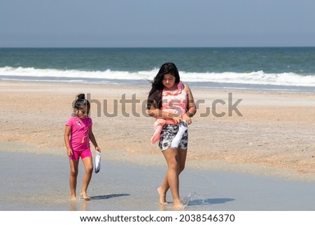 Camilla and Natalia Sandoval walk through a puddle of standing water looking for sea shells while the waves break in the background Foto stock ©