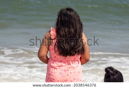 Camilla Sandoval faces the water and looks out toward the horizon on a clear sunny day she is wearing a pink top and her hair is slightly blown by the  wind Her sister can be seen below Foto stock ©