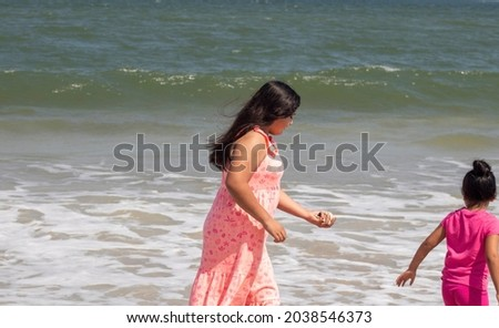 Camilla Sandoval passes a hand full of sand and sea shells to her sister Natalia in front of swelling waves on a bright summer day Foto stock ©