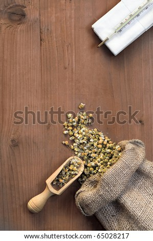 camomile and thermometer on wooden basis
