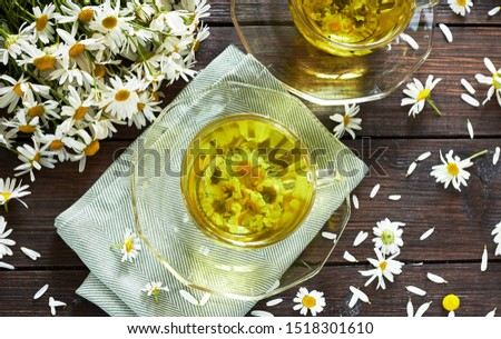 Camomile herbal tea or decoction with flower buds nearby on wooden table with textile and chamomile bouquet, closeup, copy space, flat lay, from above overhead top view,healthy, natural healer concept