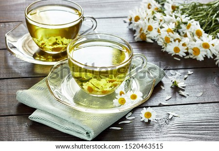 Camomile herbal tea or decoction with flower buds nearby on wooden table with textile and chamomile bouquet, closeup, copy space, healthy herbs and natural healer concept