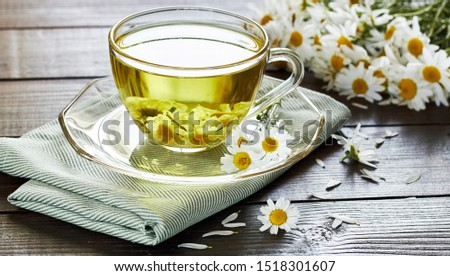 Camomile herbal tea or decoction with flower buds nearby on wooden table with textile, closeup, copy space, healthy herbs and natural healer concept